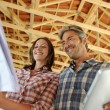 Cheerful couple standing inside house under construction — Stock Photo #13930681