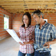 Cheerful couple standing inside house under construction — Stock Photo #13930684