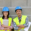 Portrait of smiling construction team standing on concrete wall — Stock Photo