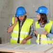 Workteam checking blueprint inside house under construction — Stock Photo