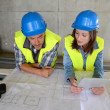 Royalty-Free Stock Photo: Workteam checking blueprint inside house under construction