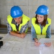 Workteam checking blueprint inside house under construction — Stock Photo #13930717