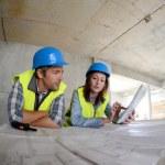 Workteam checking blueprint inside house under construction — Stock Photo
