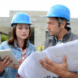 Construction team reading plan on site - Stock Photo