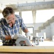 Man using electric saw inside house under construction — Stock Photo #13930747