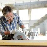 man använder elektriska såg inne i hus under uppbyggnad — Stockfoto #13930747