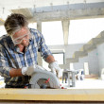 man använder elektriska såg inne i hus under uppbyggnad — Stockfoto