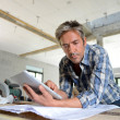 Stock Photo: Entrepreneur in house under construction checking plan