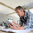 Постер, плакат: Entrepreneur in house under construction checking plan