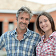 Happy couple standing in front of house under construction — Stock Photo #13930775