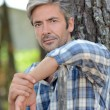 Portrait of middle-aged mstanding against tree — Stock Photo #13930778
