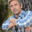 Portrait of middle-aged mstanding against tree — Stock Photo #13930790