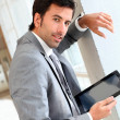 Businessman standing in hall with electronic tablet — Stock Photo #13931339