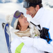 Couple standing on a snowy mountain in ski outfit — Stock Photo