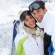 Couple standing on a snowy mountain in ski outfit — Stock Photo #13931841