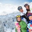 Family of four at the mountain in winter - Stock Photo