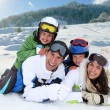 Happy family laying down in the snow — Stock Photo