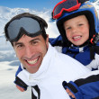 Father carrying son on his back at the mountain - Stock Photo