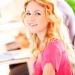 Beautiful blond girl working on laptop computer — Stockfoto