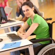 Young woman in wheelchair working in office — Stok fotoğraf