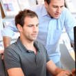 Workmates in office in front of desktop — Stock Photo