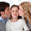 Portrait of parents kissing their daughter — ストック写真