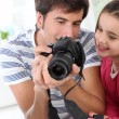 Father teaching little girl how to use camera — Stock Photo