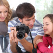 Stock Photo: Family looking at pictures on camerscreen