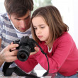 Father teaching little girl how to use camera — Stock Photo #13932682