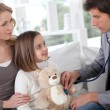 Stock Photo: Sick little girl holding teddy bear while doctor check her