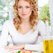 Portrait of blond woman sitting by pasta dish - Stock Photo