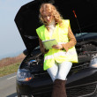 Woman standing by broken down car — Stock Photo