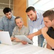 Educator with students in architecture working on electronic tablet — Stock Photo #13933106