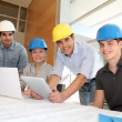 Educator with students in architecture working on electronic tablet — Stock Photo #13933117