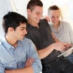 Friends in school corridor using electronic tablet — Stock Photo