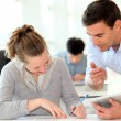 Teacher with student girl writing assignment — Stock Photo