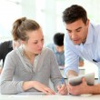 Teacher with student girl writing assignment — Stock Photo #13933229