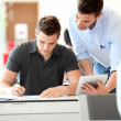 Teacher with tablet helping student with exam — Stock Photo