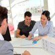 Couple in real-estate agency signing property loan contract — Stock Photo