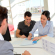 Stock Photo: Couple in real-estate agency signing property loan contract