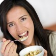 Beautiful brunette eating cereals in the morning — Stock Photo #13934562