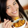Cheerful woman eating corn flakes for breakfast — Stock Photo