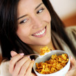 Cheerful woman eating corn flakes for breakfast — Stock Photo #13934573