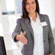 Portrait of beautiful smiling hostess giving handshake — Stock Photo #13934663