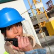 Site manager using walkie-talkie on building site - Stock Photo