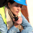 Site manager using walkie-talkie on building site — Foto Stock