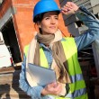 Architect on building site using electronic tablet — Stock Photo