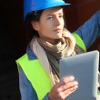 Architect on building site using electronic tablet — ストック写真