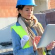 Architect on building site using electronic tablet — Stockfoto