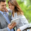 Stock Photo: Couple standing in park with electronic tablet
